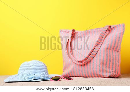 Summer bag with sunglasses and hat on beach sand