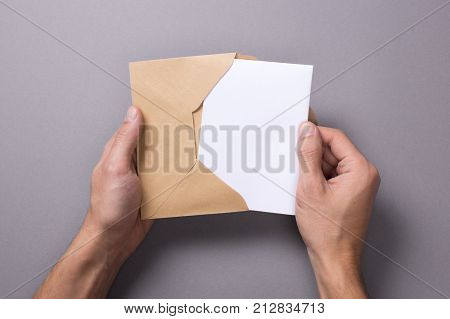 Man holds a mock-up letter or postal card with an envelope on a gray background. A man takes out or puts a letter poster