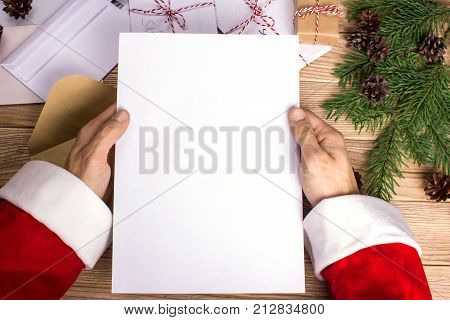 Santa Claus reads letters and holds them in his hands. Mock-up letter format A4