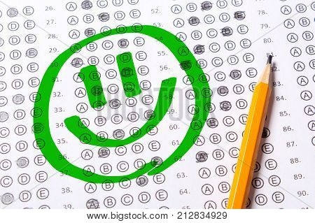 Correctly positively passed test face with a smile. Blank multiple choice answer sheet filled with pencil
