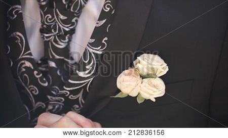 Carnation flower in a pocket. the flower in jacket pocket. pin with decorative white flowers pinned on the groom's jacket. boutonniere flower in the pocket of the groom on wedding ceremony