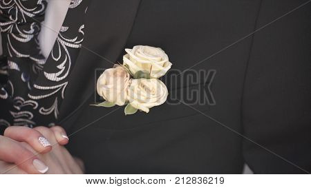 Carnation flower in a pocket. the flower in jacket pocket. pin with decorative white flowers pinned on the groom's jacket. boutonniere flower in the pocket of the groom on wedding ceremony HD