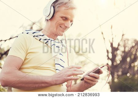 Music playlist. Joyful positive elderly man using MP3 player and choosing a song while wearing headphones