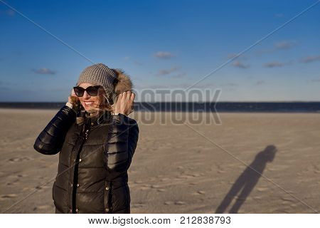 Trendy woman in a warm autumn outfit with sunglasses standing on a beach at sunset casting a long shadow across the sand looking to the side with a happy smile
