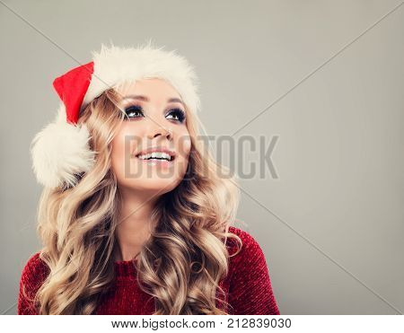 Christmas Woman in Santa Hat on Banner Background. Happy Model with Blonde Hair and Makeup Smiling. New Year or Christmas Concept