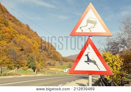Warning Road Signs About Slippery Road And Wild Animals