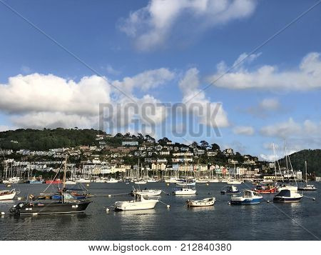 Dartmouth, Devon, UK. July 27th  2017. View of Dartmouth harbour with yachts and sailboats with quaint Darthaven town to the rear overlooking the bay area with a blue sky.