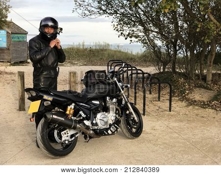 Brownsea Island, Poole, Dorset, United Kingdom. 6th October 2017. Motorbike rider in black leathers and helmet with Go Pro video camera at Brownsea Island, Dorset, UK and Yamaha XJR 1300 motorbike.
