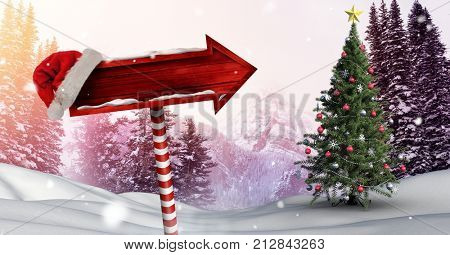 Digital composite of Wooden signpost in Christmas Winter landscape and Santa hat with Christmas tree