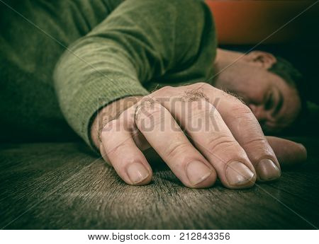 Man's hand close-up. Drunk or dead man lies on floor