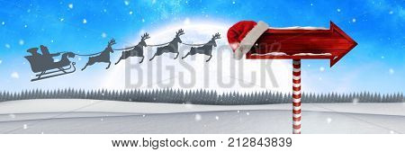 Digital composite of Wooden signpost in Christmas Winter landscape and Santa's sleigh and reindeer's