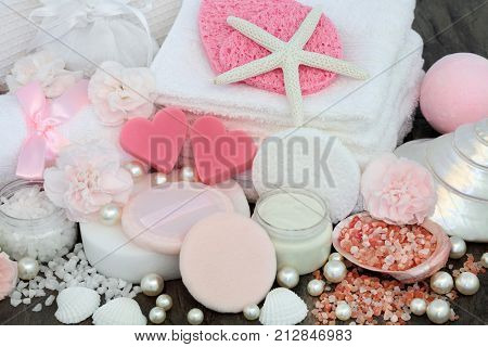Skincare and body care beauty treatment including pink heart shaped soaps, himalayan exfoliating salt, sponges, face cloths, moisturizing lotion, powder puffs, and carnation flowers.