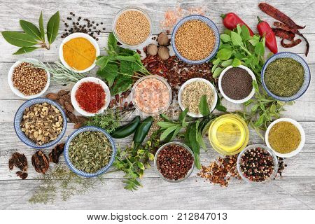 Spice and herb seasoning with fresh and dried herbs and spices, including chili pepper selection, mustard powder and seeds, ground and whole peppercorns and olive oil on rustic wood. Top view.