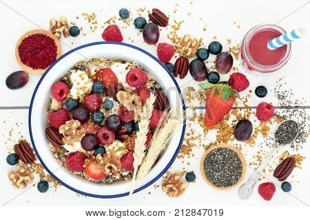 Macrobiotic health food for breakfast concept including acai berry smoothie and powder, granola, pollen grain,  berry fruit, chia seed and nuts, high in protein, omega 3,  antioxidants and vitamins.