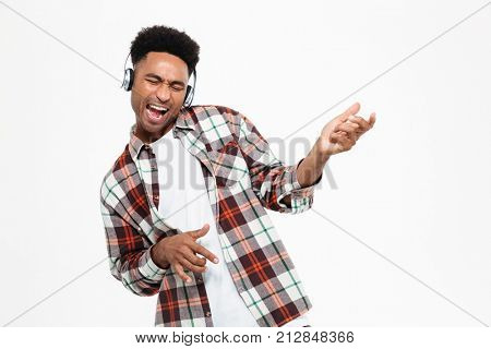 Portrait of a happy young afro american man listening to music with headphones and playing on invisible guitar isolated over white background