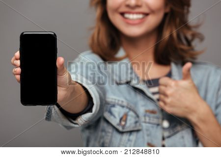 Close up portrait of a smiling teenage girl dressed in denim jacket holding blank screen mobile phone and showing thumbs up gesture isolated over gray background. focus on mobile phone