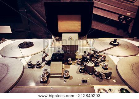 Film tape spooled on vintage cinematic reel. Retro movie equipment. Film industry.