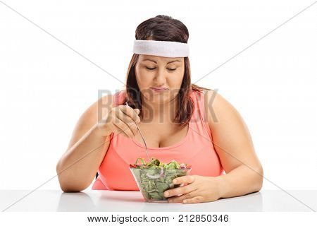 Sad overweight woman sitting at a table and looking at a bowl of salad isolated on white background
