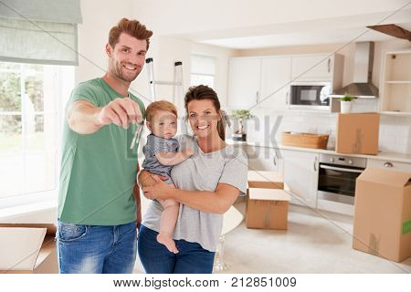 Portrait Of Family With Baby Holding Keys On Moving In Day