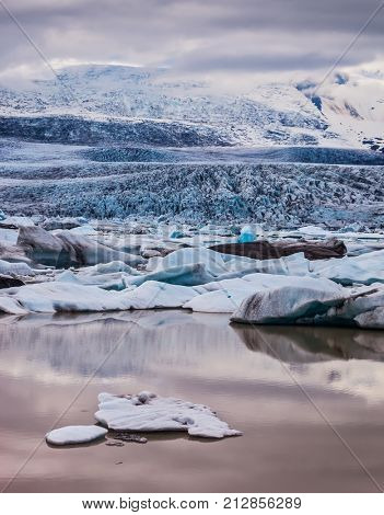The grand spectacle - sunset over the glacier Vatnajokull - the biggest glacier in Iceland. Glacier provides water Ice Lagoon Jokulsarlon. The concept of extreme northern tourism