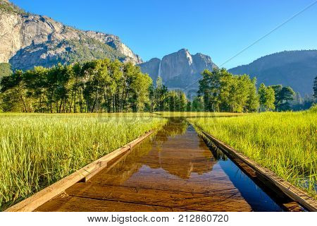 Meadow with flooded boardwalk in Yosemite National Park Valley with Yosemite Falls. California, USA.