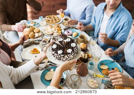 Young female bringing birthday cake with cream dollops on plate for her guests