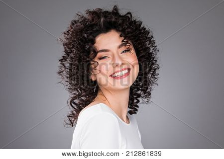 Portrait of amazing beautiful smiling woman with curly hair on gray background with copy space
