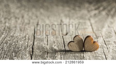Two small hearts on old wood background