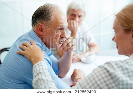 Senior man sharing his trouble with understanding friends who care