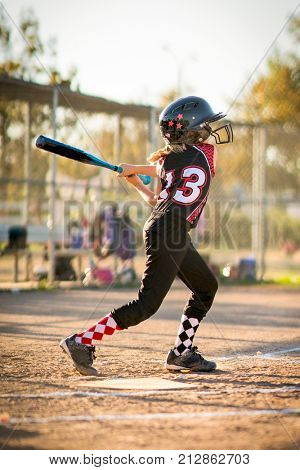 Child playing softball or baseball game