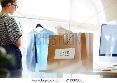 Paperbag with sale announcement on workplace of self-employed shop assistant of boutique