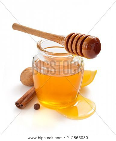 glass jar of honey and dipper isolated on white background