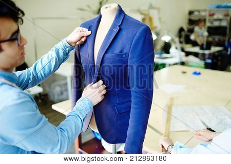 Self-employed designer of clothes looking at blue jacket on dummy during work