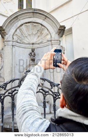 Brussels, Belgium - April 2015: Tourist Taking Photo Of Manneken Pis Or Little Man Pee, A Landmark S