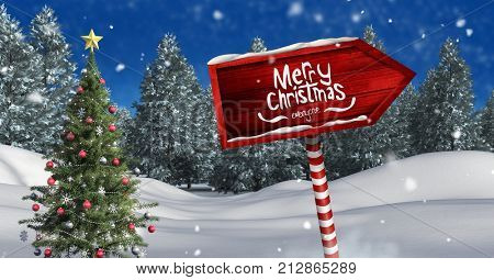Digital composite of Merry Christmas text and Wooden signpost in Christmas Winter landscape with Christmas tree