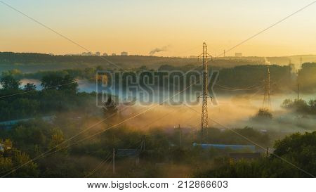 Early morning at suburbs, with power lines in the mist.