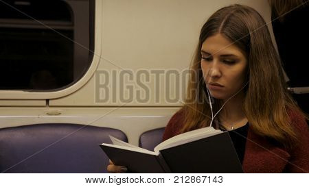 Beautiful girl reading a book in train at the subway. Teenager girl read a book in train or subway car 4K