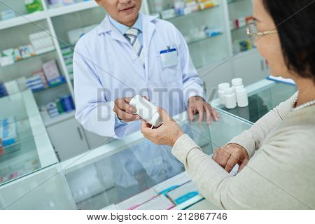 Cropped image of pharmacist selling supplements to the customer
