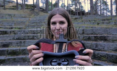 Portrait of happy girl in red coat giving virtual reality headset. Virtual Reality 360 video and 3D video app with VR glasses outdoors. Women having fun with vr glasses. Autumn season 4K