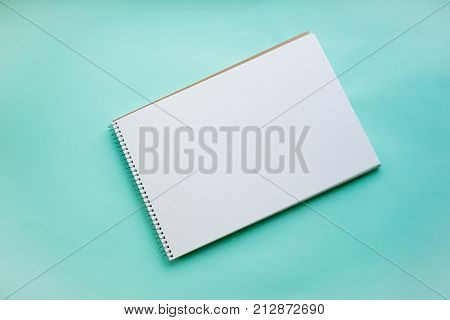 An empty sheet of sketchbook or album for drawing on a pink blue background. Drawing a still life. Flat lay stock photo. Creativity concept