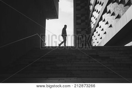 silhouette of a walking man in a city. black and white photo