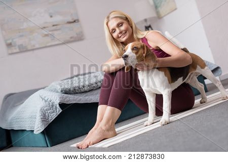 sporty middle aged woman stroking dog while sitting on yoga mat at home