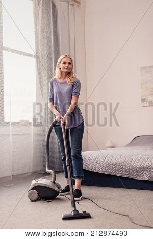 full length view of beautiful middle aged woman using vacuum cleaner at home