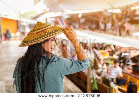 Close up portrait young asian woman with Damnoen Saduak floating market background Ratchaburi Province Thailand