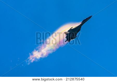 Battle Fighter Jet Aircraft Flying Dives Breaking Clouds On A Blue Sky.