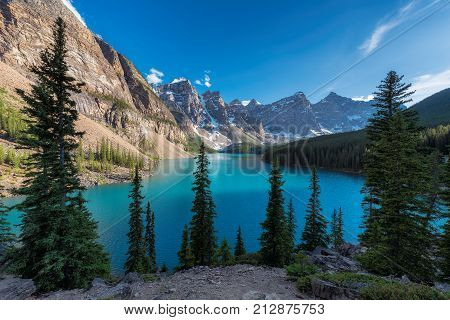 Beautiful sunset at Moraine Lake with snow-covered peaks above it in Rocky Mountains, Banff National Park, Canada.