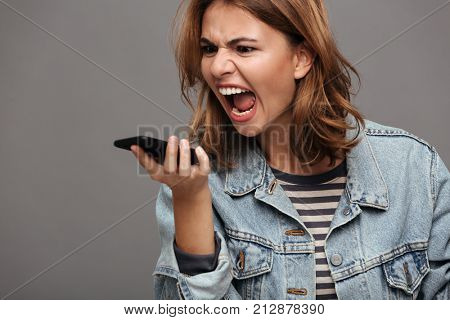 Close up portrait of an angry stressed teenage girl dressed in denim jacket yelling at mobile phone isolated over gray background