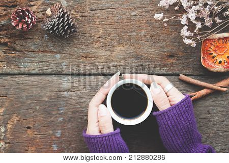 Woman hands holding cup of hot coffee on wooden table Overhead view fall and winter concep
