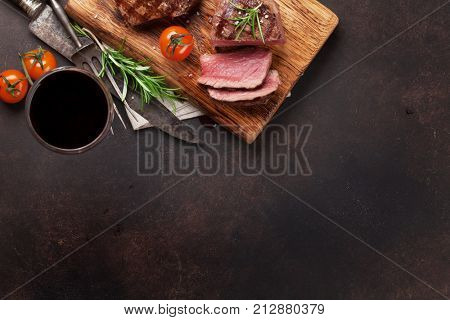 Grilled fillet steaks on cutting board and glass of red wine. Top view with space for your text