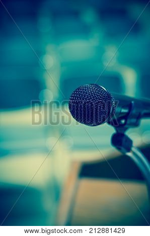 Closeup Microphone on the speech podium over the Abstract blurred photo of conference hall or seminar room background